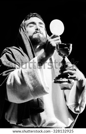 Jesus Christ praying to God consecration the bread and wine in the dark black night - stock photo