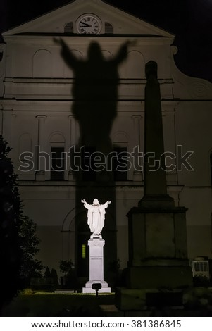 Jesus Christ statue behind St. Louis Cathedral in New Orleans, Louisiana by night - stock photo