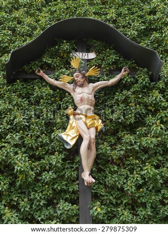 Jesus cross on a ivy-covered facade - stock photo