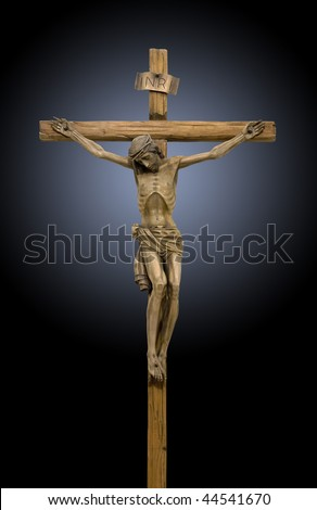 Jesus crucified on the cross, a wooden statue on black background - stock photo