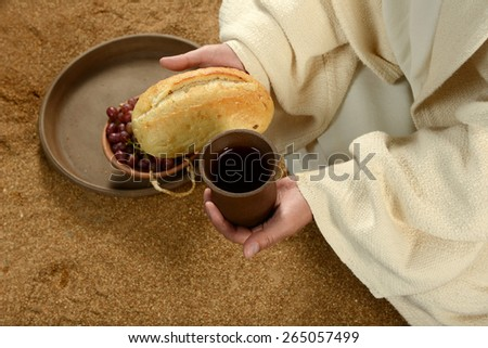 Jesus during communion holding bread and wine - stock photo