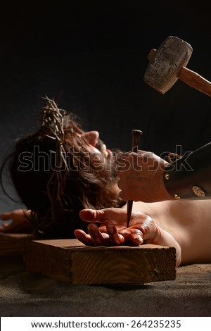 Jesus hand being nailed to the cross by Roman soldier - stock photo