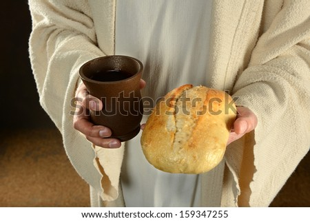 Jesus hands holding bread and wine over dark background - stock photo