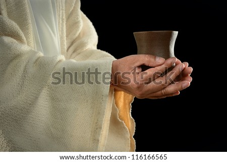 Jesus hands holding cup over dark background - stock photo