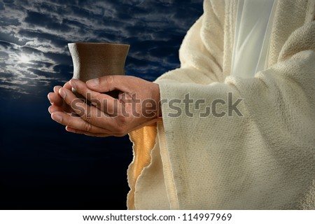 Jesus hands holding cup with night background - stock photo