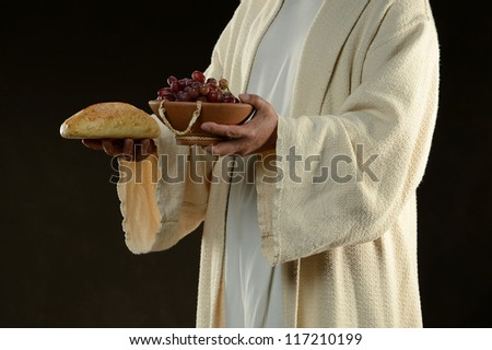 Jesus holding a bread and grapes as a metaphor - stock photo