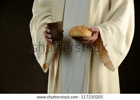 Jesus holding bread and a cup of wine as a metaphor - stock photo