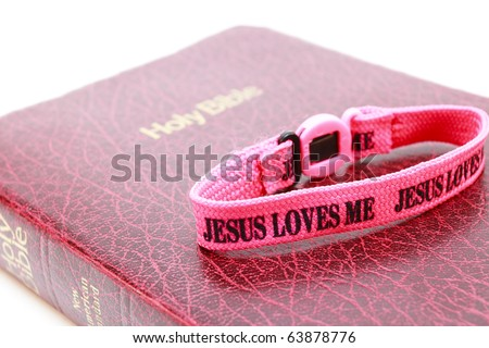 Jesus Loves the Bible A bible with a Jesus Loves Me wristband. Horizontal. - stock photo