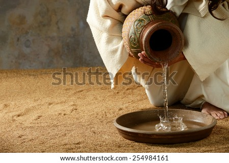 Jesus pouring water from a jar before the feet washing - stock photo