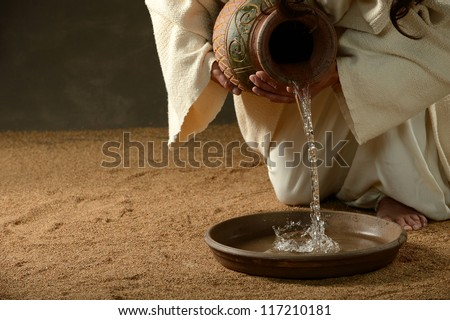 Jesus pouring water from a jug (with copyspace for text) - stock photo