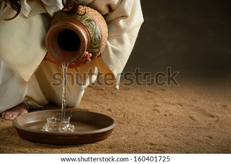 Jesus pouring water from jug over dark background - stock photo