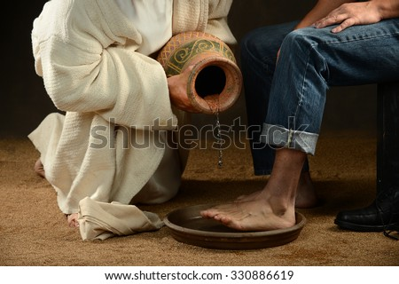 Jesus pouring water to wash feet of modern man over dark background - stock photo