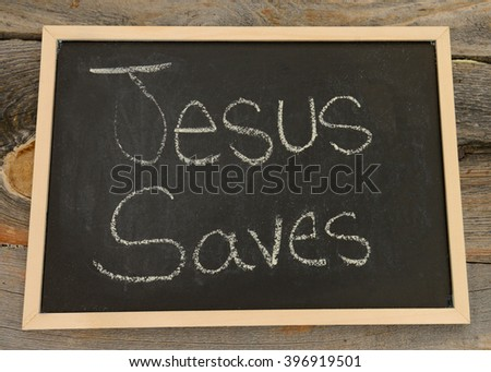 Jesus saves written in chalk on a chalkboard on a rustic background - stock photo