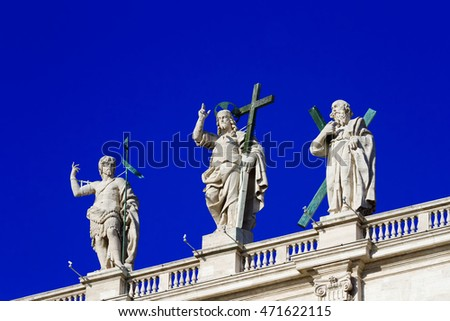 Jesus sculptures and sacred, standing on a roof of the Papal Basilica of Saint Peter, Vatican, against the blue sky