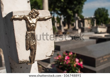 Jesus' statue on the profile of a cross in cemetery - stock photo