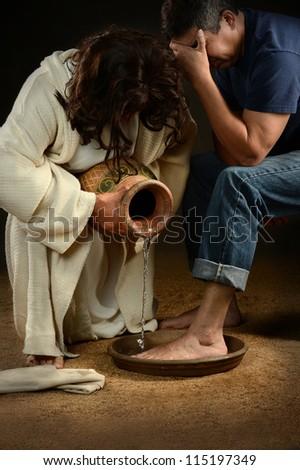 Jesus washing feet of man wearing jeans - stock photo