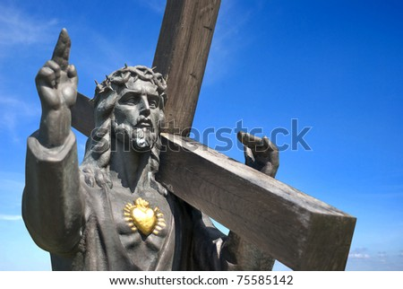 jesus with golden heart holding cross on blue sky background - stock photo