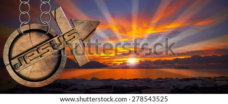 Jesus Wooden Symbol with Cross at the Sunset. Wooden symbol with cross and arrow upward and text Jesus. Hanging from a chain at a beautiful sunset over the sea with cloudy sky - stock photo