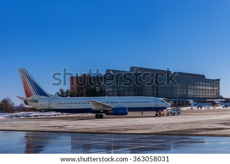 Jet aircraft being pushed back from a hangar on the runway at Vnukovo Airport - Moscow, February 18, 2015 - stock photo