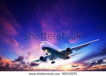 Jet aircraft cruising in a sunset sky - stock photo