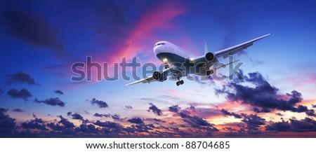 Jet aircraft cruising in a sunset sky. Panoramic shot. - stock photo