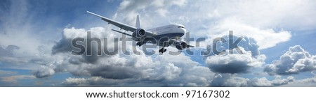 Jet aircraft in a blue cloudy sky is maneuvering for landing. Panoramic composition in high resolution. - stock photo