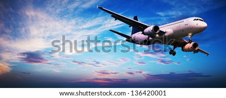 Jet aircraft in a sunset sky. Panoramic composition. - stock photo