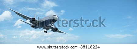 Jet aircraft is maneuvering for landing. Panoramic composition with a lot of copy space. - stock photo