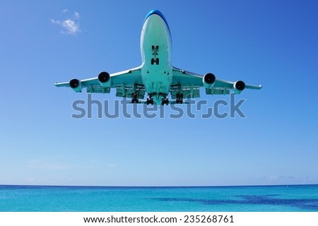 Jet aircraft on landing approach flying low over water - stock photo