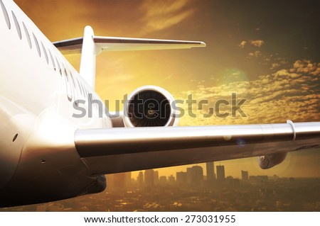 Jet airplane flying over city. Focus on the wing - stock photo