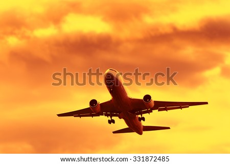 Jet Airplane In Flight At Sunset Time - stock photo