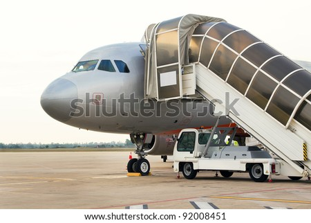 Jet airplane loading on tarmac in topical Siem Reap, Cambodia. Shadowy figures visible through the frosted panels of the portable gangway. - stock photo