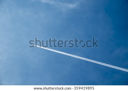 jet airplane with trail of fuel against blue sky - stock photo