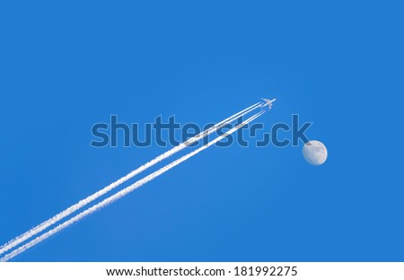jet airplane with trail of fuel on blue sky and big moon - stock photo