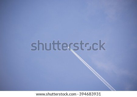 jet and its vapour trails in a cloudy blue sky - stock photo