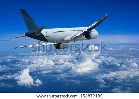 Jet cruising above the clouds - stock photo