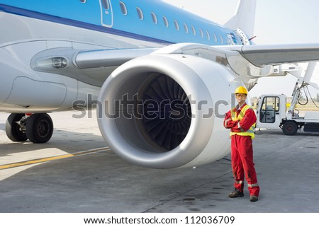 Jet engine mechanic posing next to a commercial aircraft on the runway - stock photo