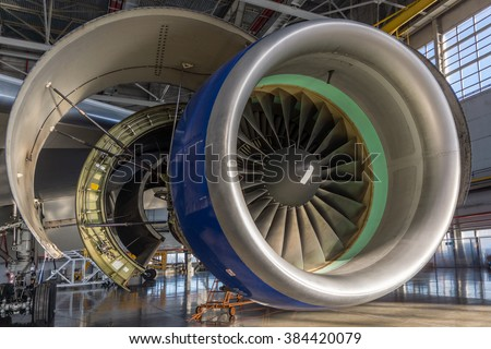 Jet engine open and ready for maintenance inside hangar - stock photo