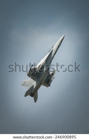Jet fighter in flight, climbing in blue sky. - stock photo