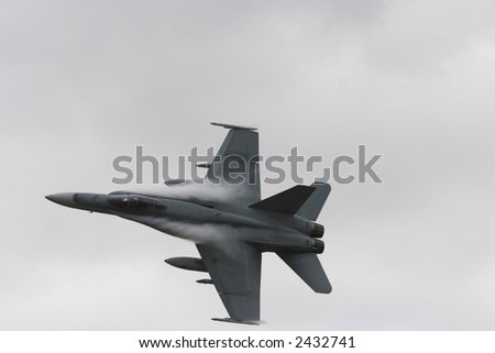 Jet Fighter with water vapour trailing off its body - stock photo
