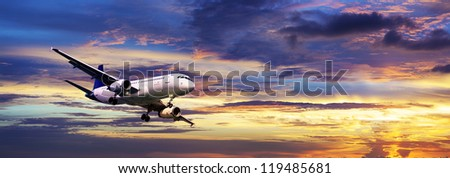 Jet is maneuvering for landing in a sunset sky. Panoramic composition. - stock photo