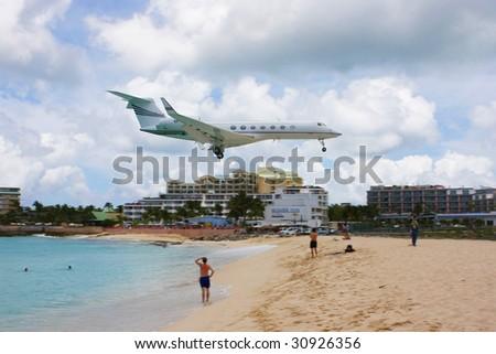 Jet landing at Maho Beach, St. Marteen - stock photo