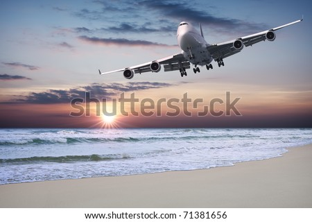 Jet liner is flying over the beach at sunset - stock photo