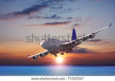 Jet liner over the sea at dusk - stock photo