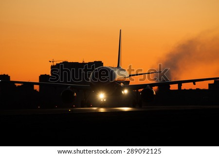 Jet on the runway at sunrise or sunset - stock photo