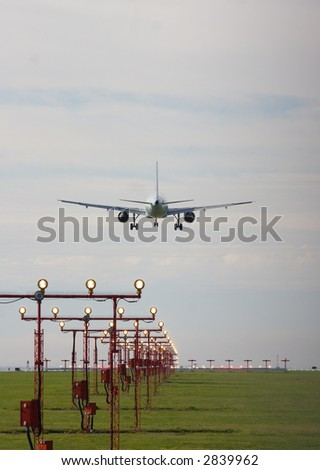 jet over runway marker lights at the Vancouver airport - stock photo