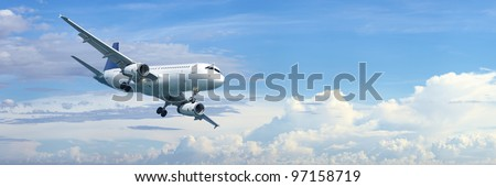 Jet plane in a blue cloudy sky is maneuvering for landing. Panoramic composition in high resolution. - stock photo