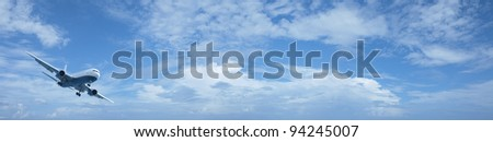 Jet plane in a blue cloudy sky. Panoramic composition in high resolution.