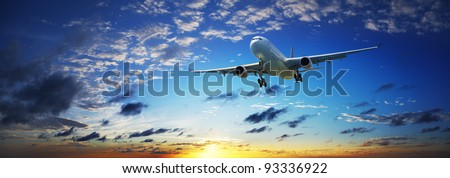 Jet plane in a sunset sky. Panoramic composition in high resolution. - stock photo