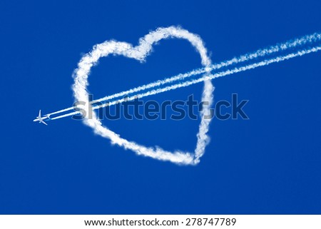 jet plane in the blue sky, and a trace of turbines, flies through the heart - stock photo
